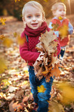 Cute little twins looking at falling down autumnal leaves - 235786708
