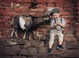 Cute little boy with a friendly goat - 235787990