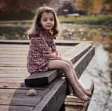Portrait of a miserable little girl sitting on a jetty - 235788720