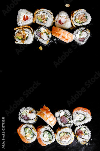 Japanese traditional sushi rolls with with different fillings. Top view, black background. Space for text