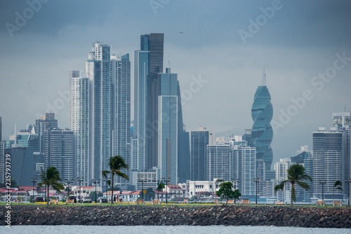 fototapeta na ścianę Hot, humid day in Panama city as another rainstorm brews quickly over the city skyline. Tall buildings shimmer in heatwaves rising in humid air. People on Panama Canal jetty park in foreground.