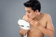 Leinwandbild Motiv Young asian male model checking his face in mirror
