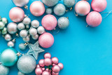 Christmas and New Year symbols. Toys for festive tree. Blue and pink balls and stars on blue background top view copy space border