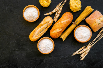 Farinaceous food. Fresh bread and raw pasta near flour in bowl and wheat ears on black background top view space for text