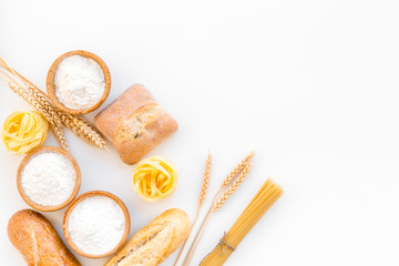 Products made of wheat flour. White flour in bowl, wheat ears, fresh bread and raw pasta on white background top view copy space