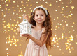 girl child is posing with lantern in christmas lights, yellow background, pink dress
