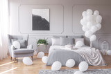 Real photo of a romantic bedroom interior with an armchair, double bed and balloons - 235847329