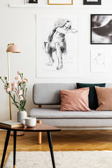 Flowers on wooden table in front of grey sofa with pillows in flat interior with posters. Real photo