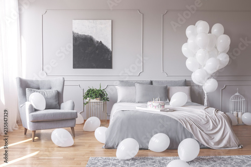 Real photo of a romantic bedroom interior with an armchair, double bed and balloons