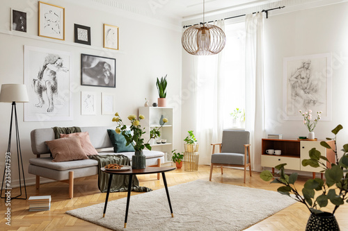 Leinwandbild Motiv Table with flowers on carpet in apartment interior with posters above sofa near armchair. Real photo