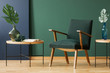 Quadro Wooden armchair between tables with leaves in green and blue living room interior. Real photo