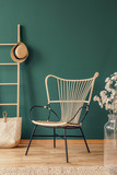 Flowers next to rattan armchair in green living room interior with hat on ladder above bag. Real photo