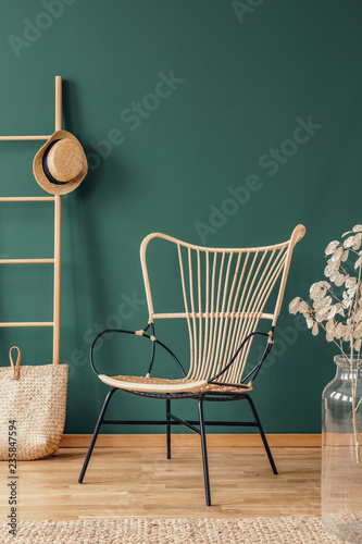 Flowers next to rattan armchair in green living room interior with hat on ladder above bag. Real photo - 235847594