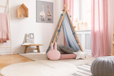 Pastel pillows in front of tent in girl's bedroom interior with pink drapes and poster. Real photo - 235847957