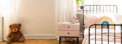 Plush toy against white wall with copy space in child's bedroom interior with bed. Real photo