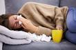 Leinwandbild Motiv Sick girl holding tissue and holding stomach and tea.