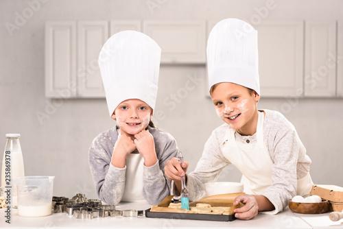 Leinwandbild Motiv joyful children in aprons brushing cookies on baking tray in kitchen