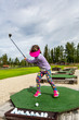 Young girl outdoors at a driving range playing golf and practice her swing.