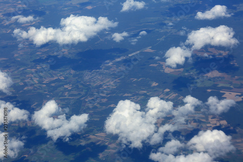 View from the plane to the clouds above the land in Europe - 235876198