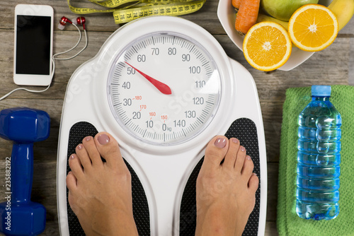 Foto Murales Healthy lifestyle concept with woman's feet having perfect weight on bathroom scale
