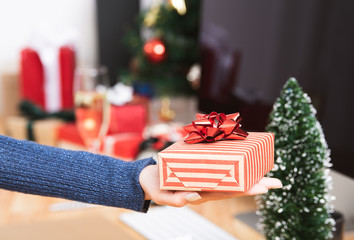 Businesswoman hand holding gift box in christmas holiday at the office with christmas decoration on table.