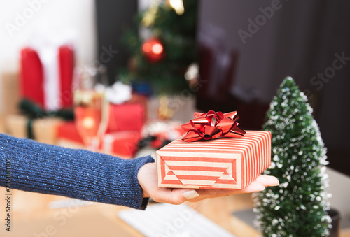 Businesswoman hand holding gift box in christmas holiday at the office with christmas decoration on table. - 235883106