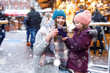 Leinwanddruck Bild - Happy kid girl and young beautiful woman with cup of steaming hot chocolate and mulled wine. Adorable child and beautiful mum on Christmas market in Germany. Family walking on Xmas market.