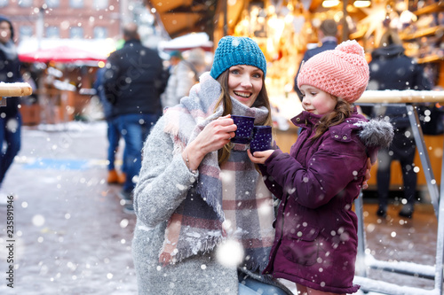 Leinwanddruck Bild Happy kid girl and young beautiful woman with cup of steaming hot chocolate and mulled wine. Adorable child and beautiful mum on Christmas market in Germany. Family walking on Xmas market.