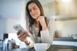Leinwanddruck Bild -  Relaxed beautiful brunette texting in modern kitchen