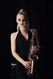 Saxophone and blonde girl holding a saxophone in her hands on a black background, portrait to the waist