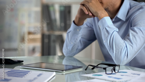 Pensive businessman using tablet, counting calculator, small business income
