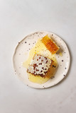 Organic honey in honeycombs in spotted ceramic plate on white marble background. Flat lay, copy space