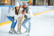 Leinwanddruck Bild - smiling parents and daughter in sweaters looking at camera on skating rink