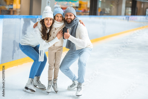 Leinwanddruck Bild smiling parents and daughter in sweaters looking at camera on skating rink