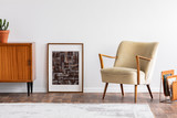 Abstract graphic in wooden frame between retro cabinet with plant and elegant beige armchair, real photo - 235928932
