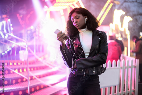 Girl checking her phone while walking in the lunapark - 235944103