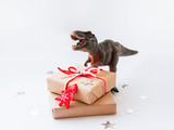 Dinosaur with presents wrapped in craft paper and red fir tree. Plastic toy with wooden symbol of Christmas and New Year. White background with star confetti.