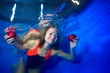 Leinwandbild Motiv Beautiful girl floating under the water on a blue background and holding red apples in her hands. She looks at the camera and smiles. Portrait. Conceptual realism