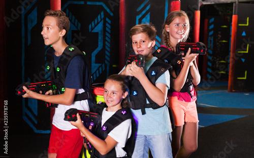 Leinwandbild Motiv Girls and boys posing with laser pistols