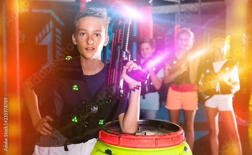 Leinwandbild Motiv Boy with laser pistol in lasertag room
