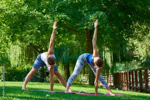 Fototapeta Young couple doing yoga outdoors