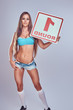 Quadro Beautiful boxing ring girl wearing a bra and shorts holding a board with a round number, isolated on a gray background.