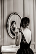 Leinwandbild Motiv portrait of beautiful young woman with comb looking at herself in the wonderful mirror . Image in black and white color style