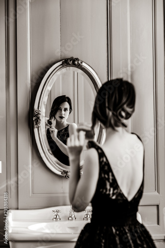 Leinwanddruck Bild portrait of beautiful young woman with comb looking at herself in the wonderful mirror . Image in black and white color style