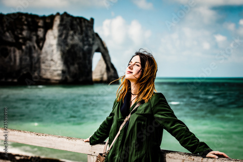 portrait of beautiful young woman standing on the wonderful cliffs and sea background - 235984918