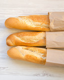 French baguettes in paper bags on white wooden surface, overhead view. Close-up.