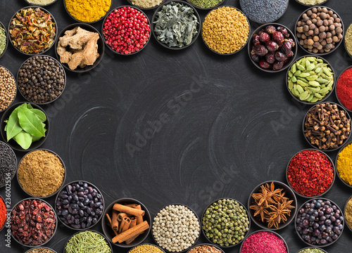 different condiments lie around. Indian spices and herbs on  black table. Seasoning with empty space for text