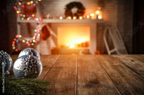 wooden table with attributes of Christmas in the glow of the fireplace    - 236008500