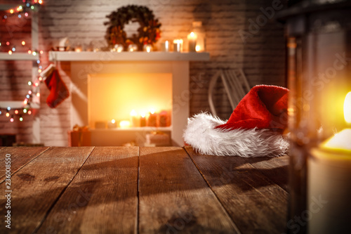 wooden table with attributes of Christmas in the glow of the fireplace    - 236008550
