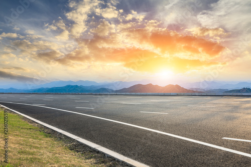 fototapeta na ścianę Asphalt road and mountains at beautiful sunset